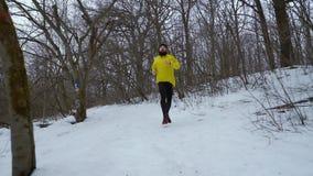 Steadicam tir? del hombre barbudo de los deportes que corr?a abajo de la colina en bosque del invierno almacen de metraje de vídeo
