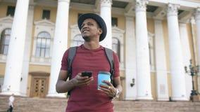 Steadicam tiró del hombre turístico sonriente que hojeaba su smartphone cerca de lugar histórico famoso en Europa almacen de metraje de vídeo