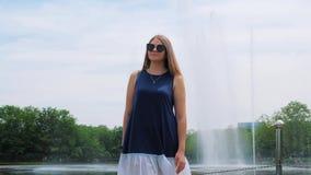 Steadicam tir? de una chica joven hermosa en gafas de sol en el parque cerca de la fuente Mujer joven sonriente linda almacen de metraje de vídeo