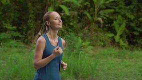 Steadicam van een jonge vrouw wordt geschoten die in een tropisch park lopen dat stock footage