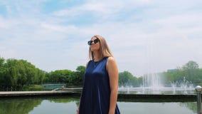 Steadicam van een mooi jong meisje in zonnebril in het park dichtbij de fontein wordt geschoten die Leuke smiley jonge vrouw stock footage