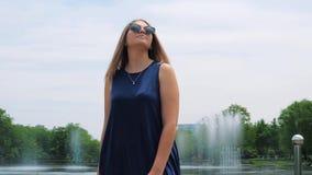 Steadicam van een mooi jong meisje in zonnebril in het park dichtbij de fontein wordt geschoten die Leuke smiley jonge vrouw stock videobeelden