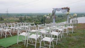 Steadicam van een verscheidenheid van wit wordt geschoten die stoelen op het ontvangstgebied vouwen van het huwelijk op de huweli stock video