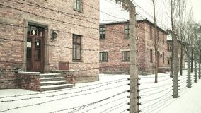 Steadicam walk along barbed wire fence of Auschwitz Birkenau concentration camp. Old brick buildings in falling snow. 4K. Video stock video footage