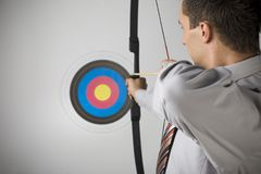 Steady... Businessman holding bow and shooting to archery target. Rear view, gray background stock image