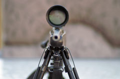 Steady aim. High powered rifle with scope on a tripod pointing at the camera stock images