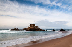 Steady as a rock. Rocks in front of the West-coast of Portugal with waves in the Atlantic Ocean as a methaphore for being steady as a rock royalty free stock photos