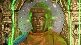 Buddhist led lighted sculpture. A steady, close up shot of a Buddhist golden sculpture lighted by a green led surrounded by shiny details stock video