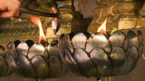 Flames in metal supports. A steady, close up shot of flames in metal supports, entertained by someone pourring oil onto them stock footage