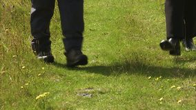 Two people walking on a lawn. A steady close up shot of  a grass as two people walks stock video
