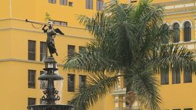 Fountain with Angel Statue On Top. Steady, exterior, medium wide shot of a fountain with an angel statue on top, next to a palm tree stock footage