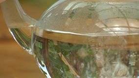 Pouring Boiling Water Into Glass Teapot. Steady, extreme close up shot of boiling water being poured into a glass teapot stock video footage