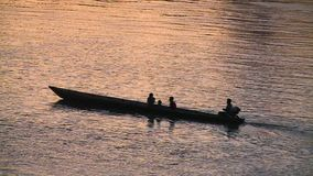 Boat on Water During Sunset. Steady, medium close up shot of a canoe-shaped boat with a trolling motor during sunset stock footage