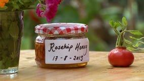 Jar Of Rosehip Honey. Steady, medium close up shot of a jar of rosehip honey next to a whole rose hip stock video footage