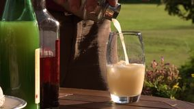 Pour Cocktail Into Glass Cup. Steady, medium close up shot of a person pouring a cocktail into a glass cup stock footage