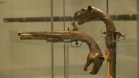 Guns with panther shaped handles. Steady, medium close up shot of two antique guns with panther shaped handles on display at a museum stock video footage