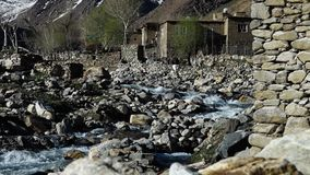 Brick houses near a river. A steady, medium shot of ancient, brick and stone houses built near a constantly flowing river stock video footage