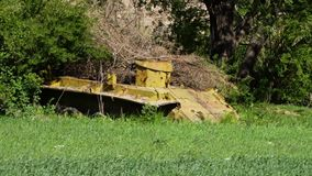 A yellow abandoned tank body. A steady, medium shot of a yellow abandoned tank body, covered with dry vegetation stock video
