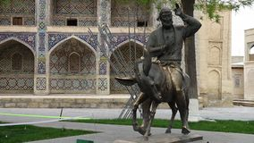 Statue of Man Riding Mule. Steady, medium wide shot of a statue of a bearded man riding a mule in front of Nadir Divan-Begi Madrasah stock footage