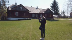 Girl tourist makes a photos of wooden house in an old European village
