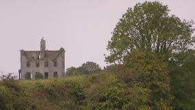 Unfinished house in Ireland. A steady shot of an unfinished rock house on top of the mountain stock video footage