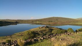 Pond with Grassy Rolling Hills. Steady, wide shot of a pond with grassy rolling hills in the background stock video footage