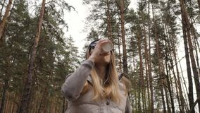Steadycam fly around shot. Woman drink coffee in the pine forest