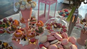 Steadycam shot of the candy bar at wedding. Table is full of different colorful candies, cake-pops, cakes, macarons and stock video footage