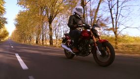 Steadycam shot of motorcyclist driving his motorbike on the road during sunset. Steadycam shot of motorcyclist driving his motorbike on the road during autumn stock footage