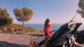 Traveling in convertible car for life. Steadycam shot of young attractive hipster couple enjoy views of ocean and mountains during honeymoon vacation in summer stock video