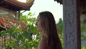 Steadycam tiró de una mujer joven que caminaba dentro de un templo budista Ho Quoc Pagoda en la isla de Phu Quoc, Vietnam almacen de metraje de vídeo
