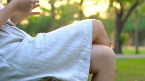 Steadycam tiró de una mujer joven que se sentaba en un parque que utiliza un teléfono celular almacen de metraje de vídeo