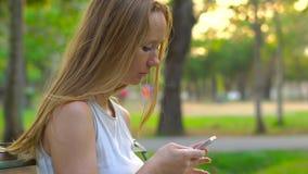 Steadycam tiró de una mujer joven que se sentaba en un parque que utiliza un teléfono celular metrajes