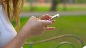 Steadycam tiró de una mujer joven que se sentaba en un parque que utiliza un teléfono celular almacen de video
