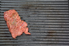 Steak. Image of a piece of steak from the meat lying on a cast-iron grill. High angle view. Space for text Royalty Free Stock Images