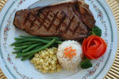 Steak. New York Steak, rice, beans, white corn, broccoli and a rose made out of tomato Royalty Free Stock Photos