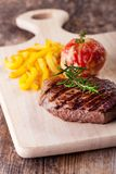 Steak. Grilled steak with fries and tomato Stock Image