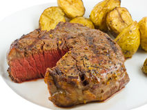 Steak. Grilled tenderloin steak slightly cut open to reveal the medium rare inside and baby potatoes stock images