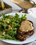 Steak with arugula. And green peppercorn sauce royalty free stock photography