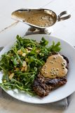 Steak with arugula. And green peppercorn sauce stock image