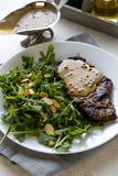 Steak with arugula. And green peppercorn sauce stock images