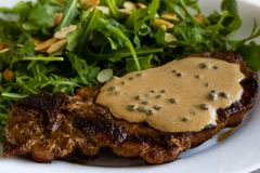 Steak with arugula. And green peppercorn sauce royalty free stock photos