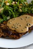 Steak with arugula. And green peppercorn sauce royalty free stock images
