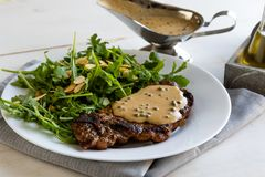 Steak with arugula. And green peppercorn sauce royalty free stock photo