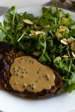 Steak with arugula. And green peppercorn sauce royalty free stock image