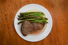 Steak and Asparagus Dinner. Delicious steak and asparagus in a buttery, hollandaise sauce on a small plate to make the portion seem larger. Full of protein Stock Images