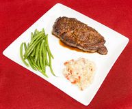 Steak au Poivre dinner plate. Steak au Poivre with haricots verts and bacon and red pepper risotto Stock Photos