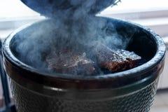 Steak auf einem runden Grill, im Rauche Horizontaler Rahmen Stockfotografie