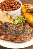 Steak with baked potato, beans and garlic bread Royalty Free Stock Photography