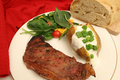 Steak and baked potato dinner Stock Photos